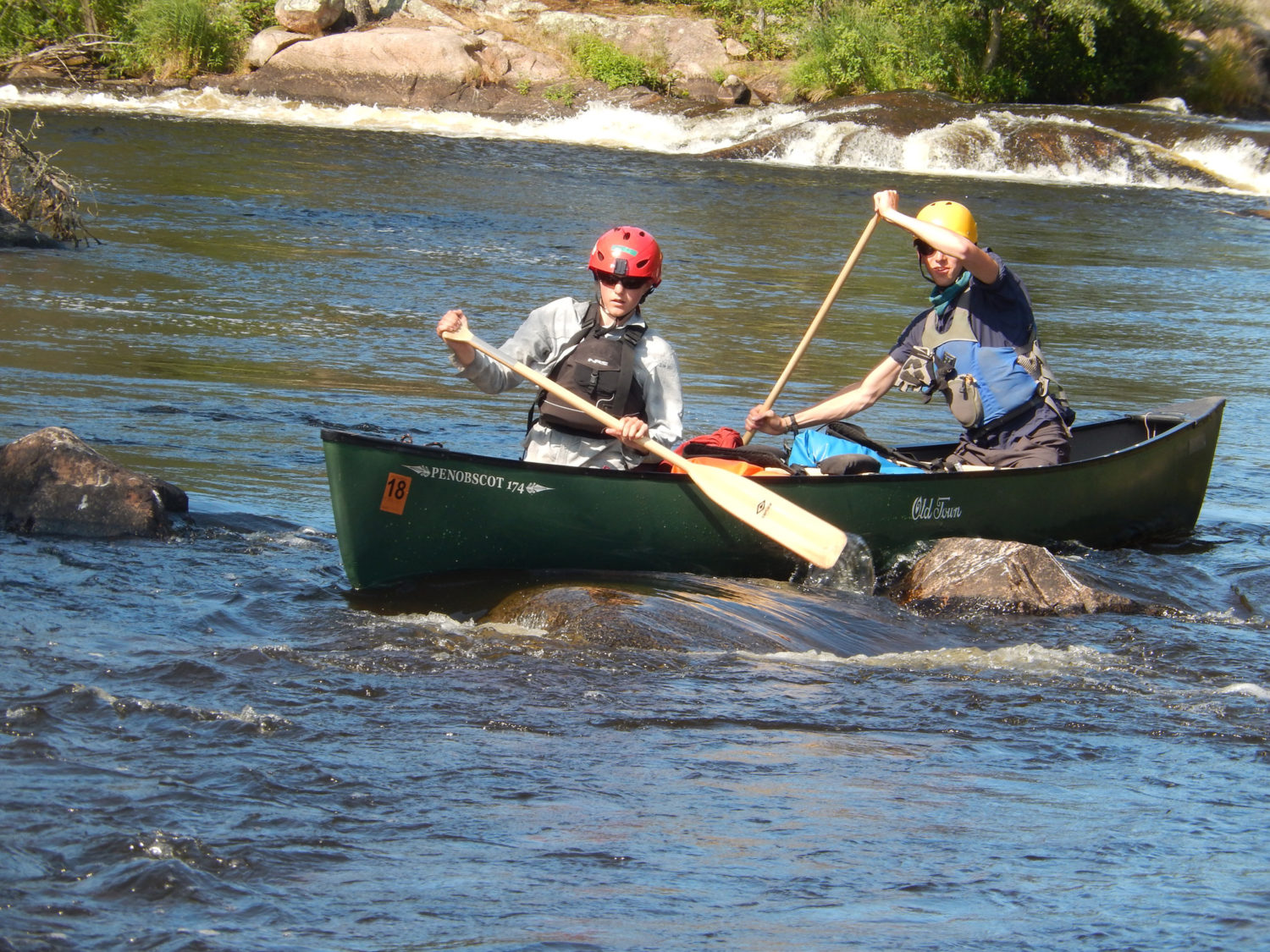 Boys rowing in a canoe on a river