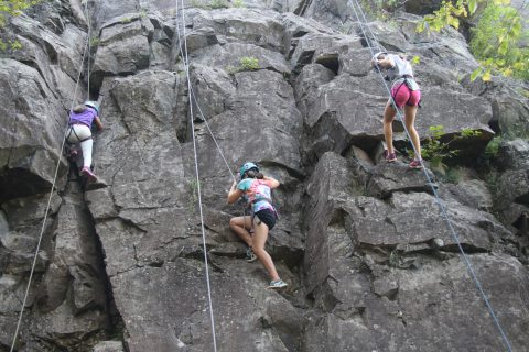 Camp Thunderbird kids climbing a rock face during adventure camp