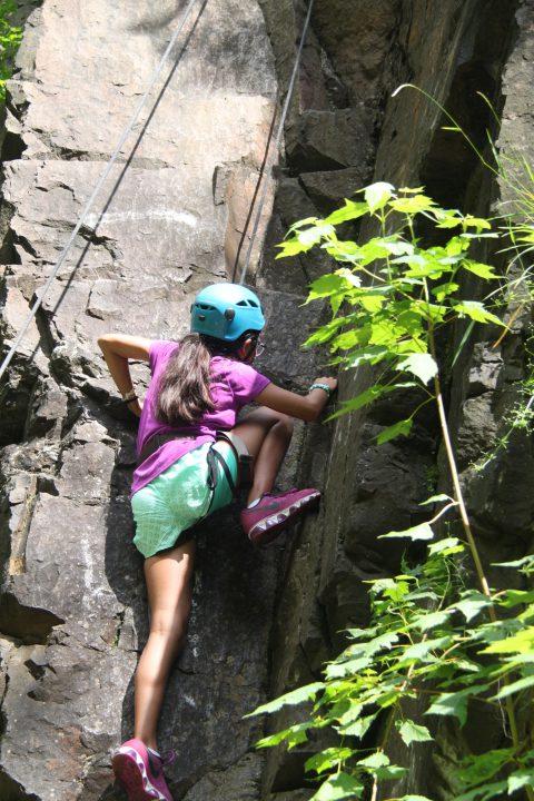 Girl climbing up a rock wall