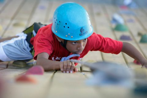Boy climbing a rock wall