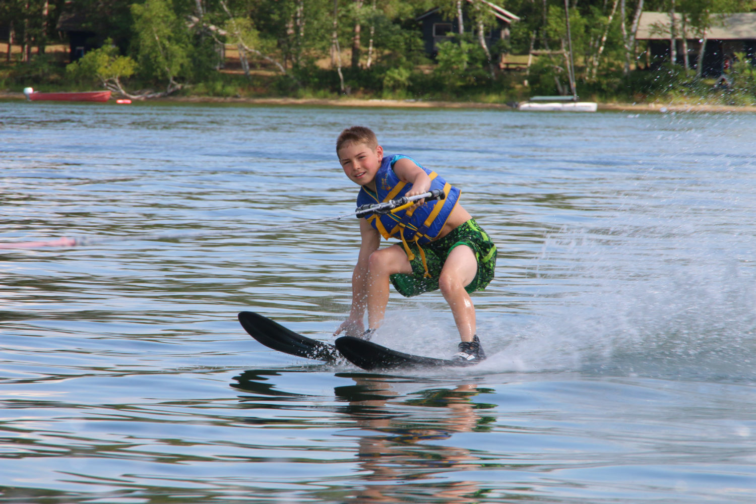 Boy water skiing on lake at Camp Thunderbird