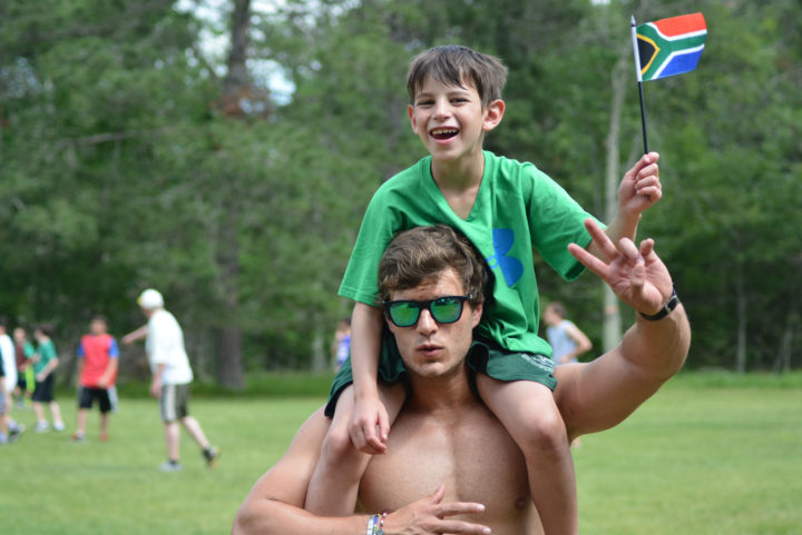 Boys camp councilor with summer camper on his shoulders