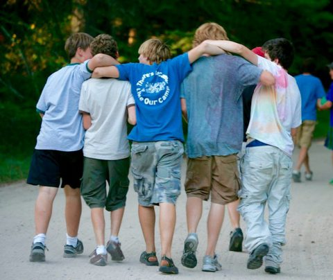 Boys walking together with arms around each other's shoulders