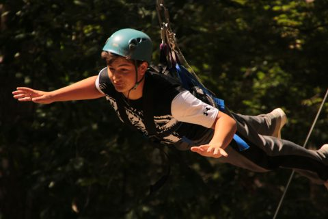 Boy doing a high ropes course at camp