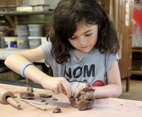 Girl making pottery at Camp Thunderbird