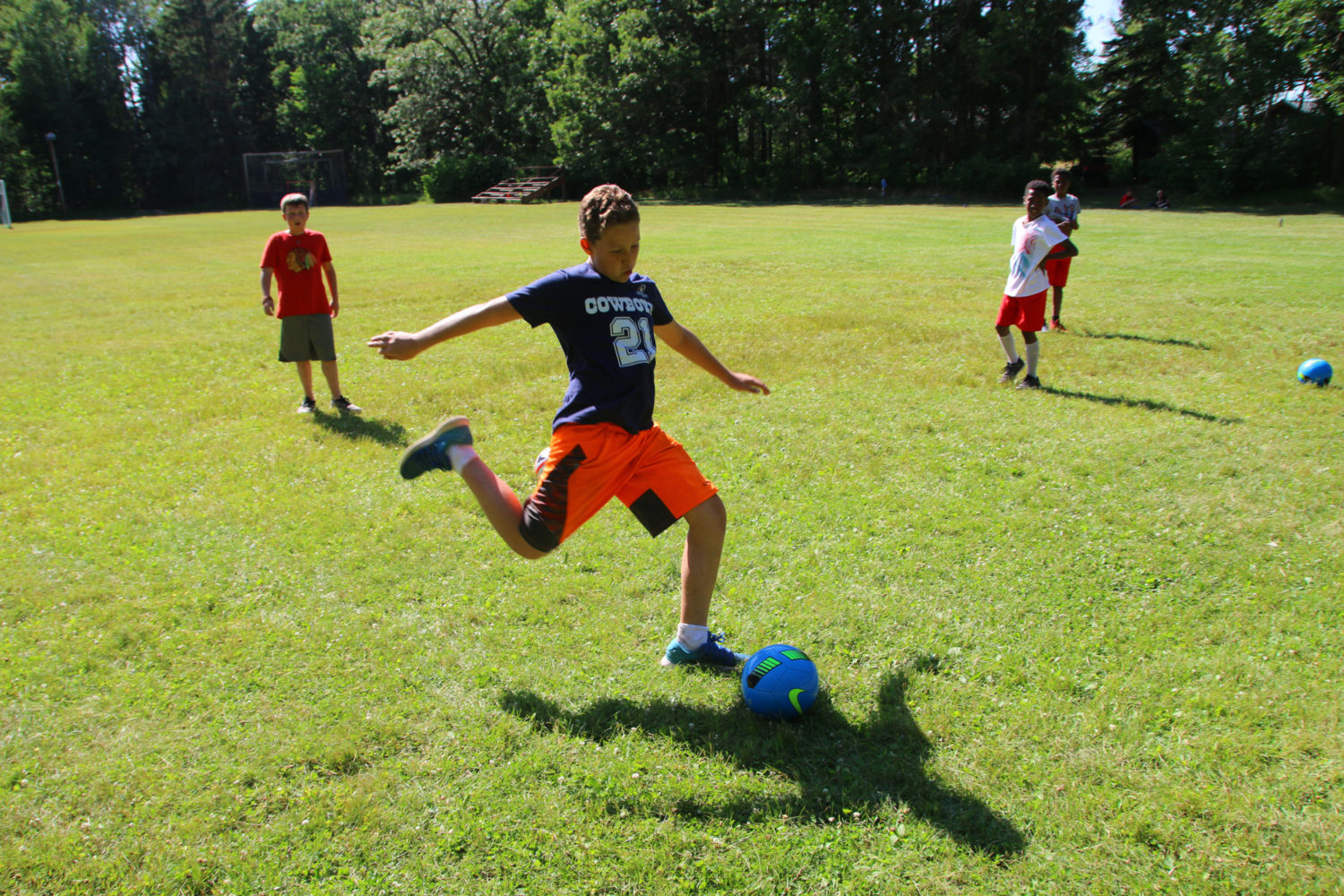 Boy kicking a soccer ball at boys summer camp