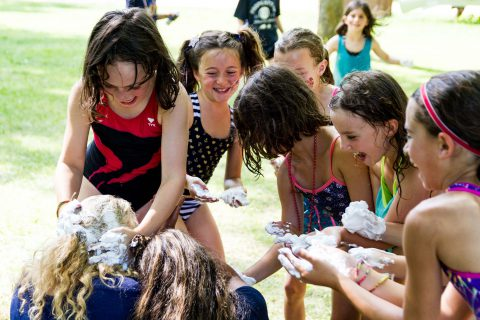 Girls having fun with a shaving cream activity at camp