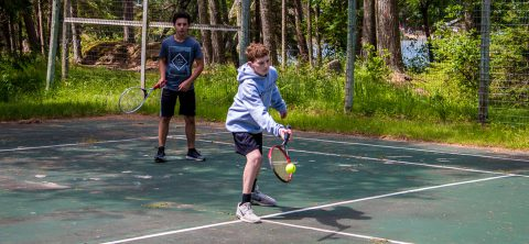 Boy playing tennis at Camp Thunderbird