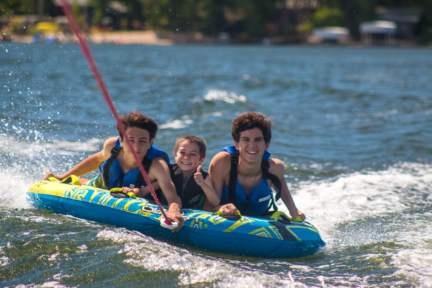 Kids water skiing behind a boat on a lake